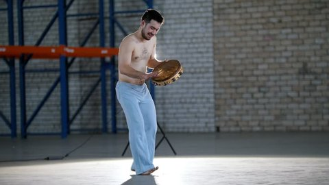 A man dancing and playing tambourine in a bright room