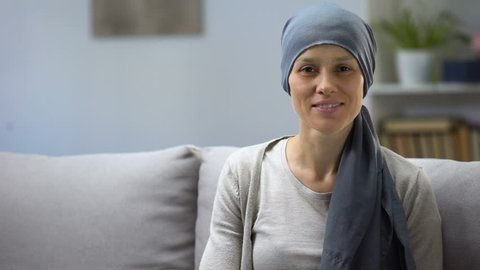 Woman recovering after chemotherapy looking at camera, survivor, background