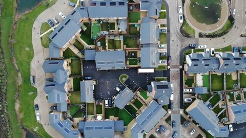 Top down view flying over modern houses, a two ponds in a contemporary new build estate in Greenhithe, Kent