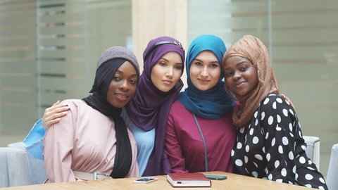 Portrait of multiracial group of muslim women dressed in national dresses and hijabs of bright colours in modern shopping centre.