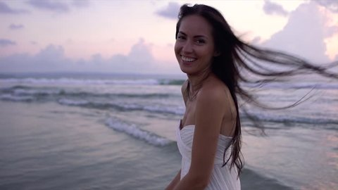 Happy smiling girl long white wet dress beach at sunset. Slow motion.