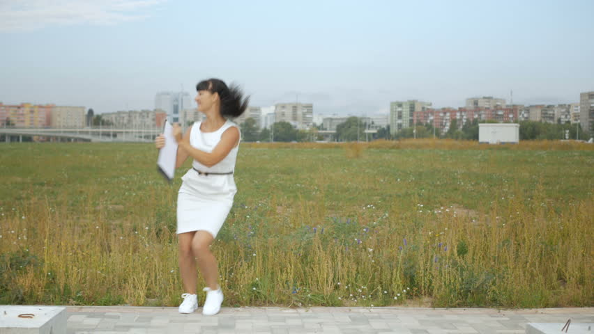 Successful business woman dances and rejoices outdoors on the outskirts of New York City. Funny Businesswoman Dancing. The girl in white dress rejoices. 4K UHD. | Shutterstock HD Video #1028472467