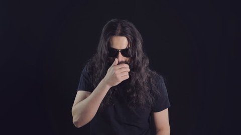 Portrait of a brunette eastern man with a long curly hair, beard and mustache in sunglasses on a black background. Man sneezes and covers his mouth