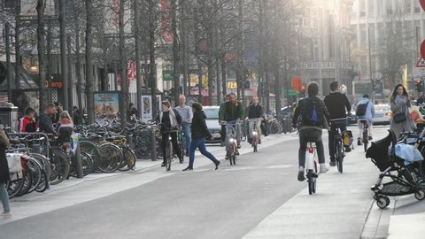 Brussels, Belgium - April 2, 2019:Wonderful view of relaxed people riding their bicycles on a historic street and a mother with a pram crossing street in Brussels in slo-mo.
