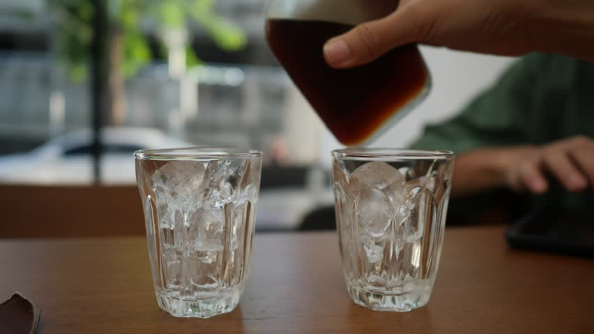 Coffee cup, Pour coffee into a glass with ice, cold brew coffee, slow-motion in 4k | Shutterstock HD Video #1028580977
