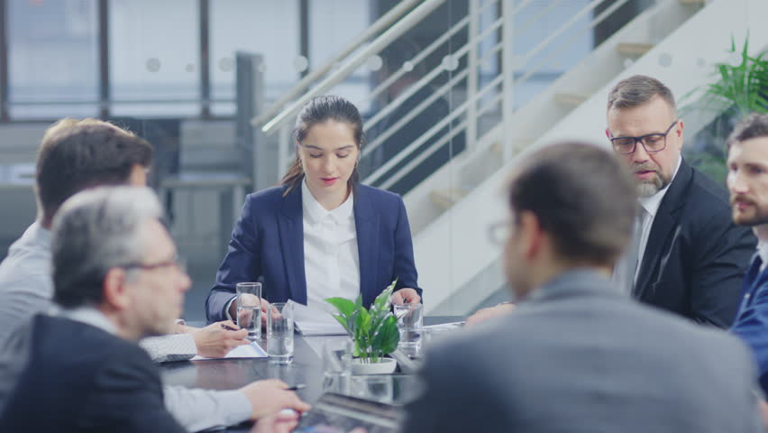 Corporate Meeting Room: Confident Female Executive Director Makes a Report to a Members of the Board and Investors about Company's Achievement of Record Breaking Annual Revenue Results | Shutterstock HD Video #1028612237