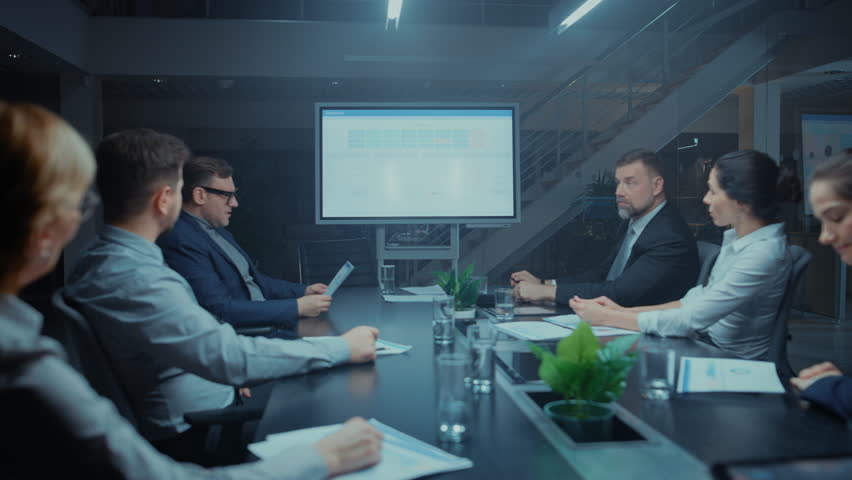 In the Modern Corporate Office Meeting Room: Diverse Group of Businesspeople, Lawyers, Executives Talking, Negotiating. They Consult Use Digital Whiteboard with Infographics and Use Documents | Shutterstock HD Video #1028612477