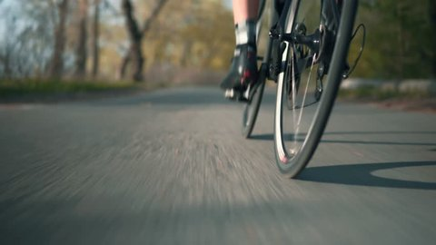 Close Up Bicycle Wheel In Motion.Cyclist Riding In Park On Road Bicycle.Cycling In City Park.Bicycle Wheel Rotate Spinning Close Up Rear View.Rear View Cycling Gear.Close Up Bike Gear.