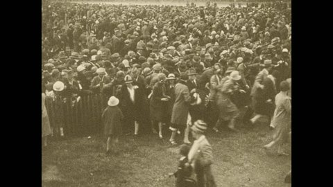 1920s: Huge crowd run to get closer to Lindbergh and his plane. Charles Lindbergh speaks into a megaphone from a balcony. Crowd waves their hats and cheers.