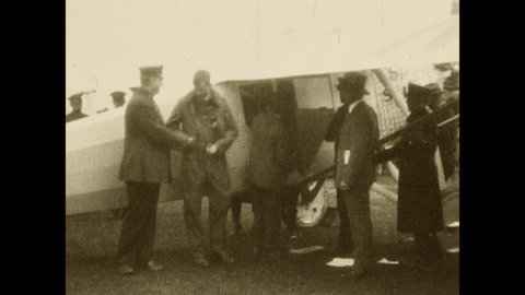 1920s: Lindbergh shakes hand with a few men by the airplane and climbs inside the small plane. Lindbergh smiles from the window.