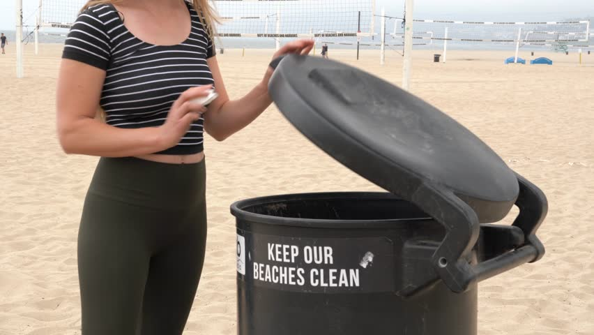 This video shows a young fit caucasian woman throwing away trash at the beach.