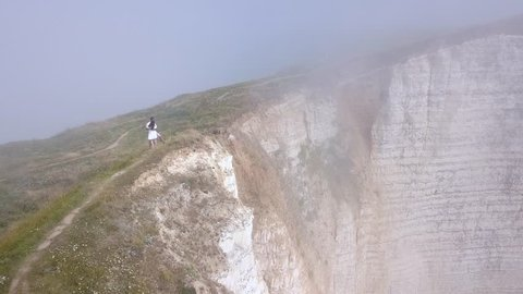 Aerial view of beautiful young couple in white clothes dancing on the top of cliff near the precipice in a heavy fog. Action Romantic stroll