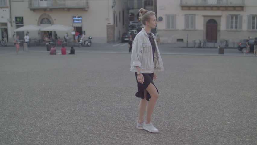 Blonde woman in urban background. Beautiful young girl wearing black elegant dress and light blue jeans jacket walking in the street. Pretty female with blonde hair.