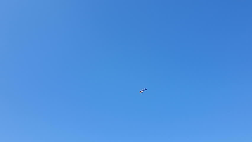 Helicopter flight against the blue cloudless sky