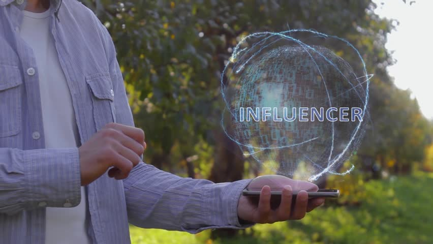 Unrecognizable man shows conceptual hologram with text Influencer. Farmer on the background of the apple orchard in casual clothes with the technology of the future mobile screen