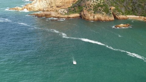 High angle tilt of power boat moving towards POV across blue water river mouth, rocky cliffs shoreline with caves and a small white lines of foam on water surface, sunny, Knysna, South Africa