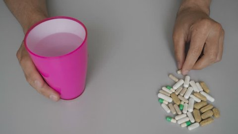 Serious man taking a pill at home. Man taking pill with water. Slow motion. Male holding  white pills with water. Closeup, close up. Person ingesting a pill and drinking it with a glass of water