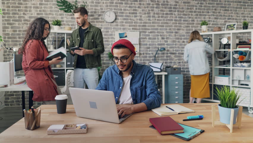 Zoom in time-lapse of creative guy employee working in office using laptop sitting at desk while coworkers are moving around. Workplace and technology concept.