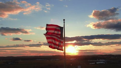 Flag of the United States in dramatic sunset,ing across the frame in front of the sun, waving in the wind, 4k UHD