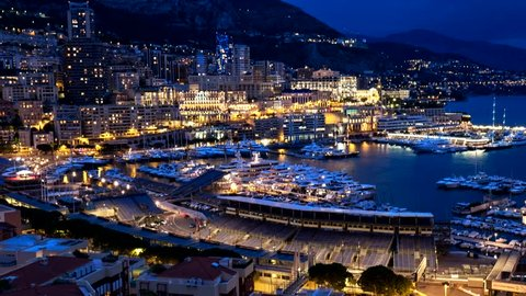 Timelapse of Monaco Monte Carlo harbour and city skyline in the evening. Monaco Port night view with fast moving clouds