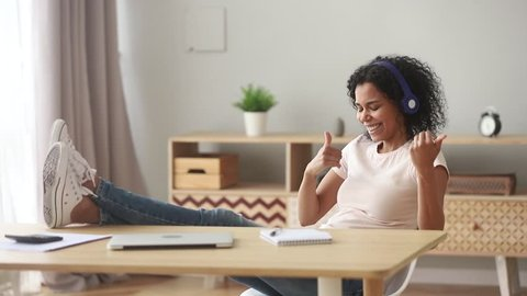 Happy african woman wear wireless headphones listening to music pretending playing guitar relaxing after work, funny funky mixed race girl feel stress free relief having fun sit at home office desk
