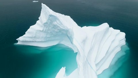Iceberg and ice from glacier in arctic nature landscape on Greenland. Aerial video drone footage of icebergs in Ilulissat icefjord. Affected by climate change and global warming.
