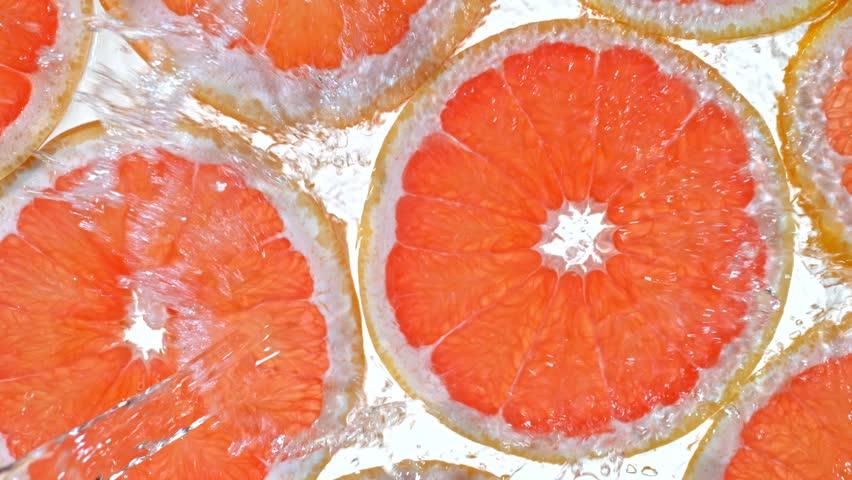 Super Slow Motion Shot of Splashing Water to Grapefruit Slices at 1000fps. #1028955317