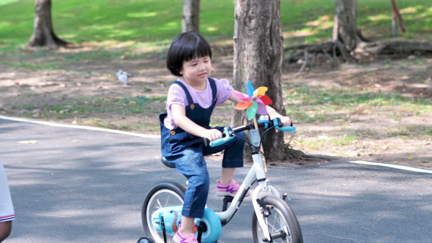 Asian cute child girl are enjoying a bike ride in the park on the street. Asian cute child girl are enjoying a bike ride in the park on the street. Slow motion | Shutterstock HD Video #1028963357