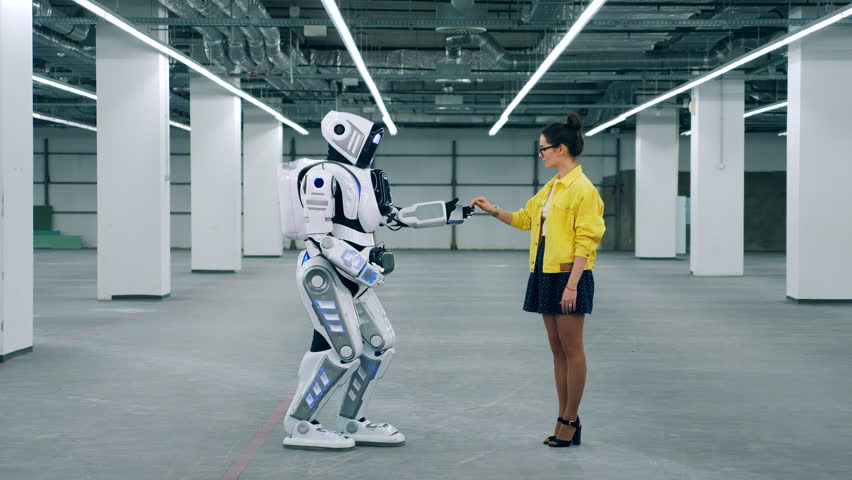 A lady is giving her hand to a tall robot | Shutterstock HD Video #1028988527