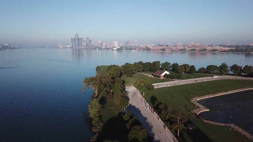 View of the Detroit skyline from Belle Isle on the Detroit river. Lake freighter passing by on a sunny summer day with blue sky. Aerial drone video of Michigan. | Shutterstock HD Video #1029027587