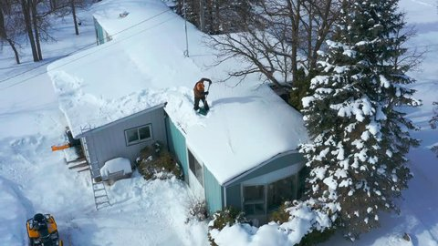 A Canadian man is seen from above as he shovels snow off the roof of a house in winter time.