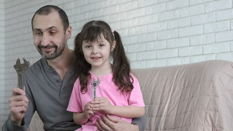 Father's day. Father with daughter with adjustable wrenches.