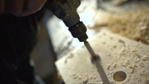 Close up of Wood Worker using an electric hand drill to drill a hole through the bracket.