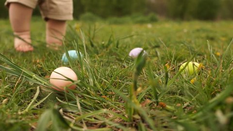 Close-up of Easter eggs in the grass against the background of the feet of a toddler collecting eggs. Easter Egg Hunt
