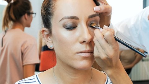 Closeup slow motion footage of professional makeup artist painting eyes and applying mascara. Visagiste preparing model for the fashion show or photoshooting. Woman using mascara and other cosmetics