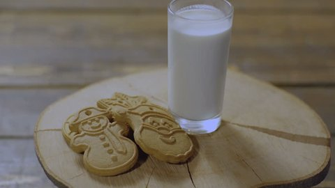 Cookies and milk for Santa Claus. Christmas cookies. Marry Christmas and Happy New Year. Milk and cookies for Santa Claus on wooden plate. Glass of milk and cookies isolated on wooden table