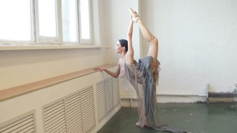 Attractive dark-haired ballet dancer female in stage costume bending back, standing on one leg doing stretching, lifting the leg up high.