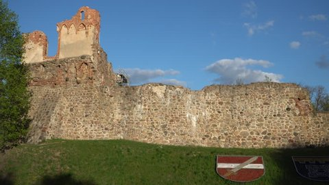 City Dobele, Latvia - spring of 2019. The stone wall of the medieval palace ruins of the Livonian Order with the shape of city blazonry on the hill. Urban landscape design.