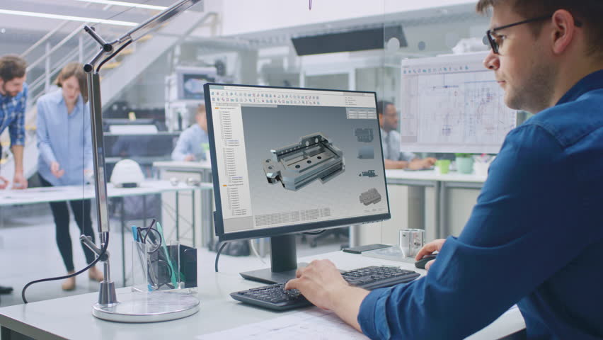 Engineer Working on Desktop Computer, Screen Showing CAD Software with 3D Component. In the Background Engineering Facility with Blueprints and Drawings with Industrial Design. Over the Shoulder   Shutterstock HD Video #1029171617
