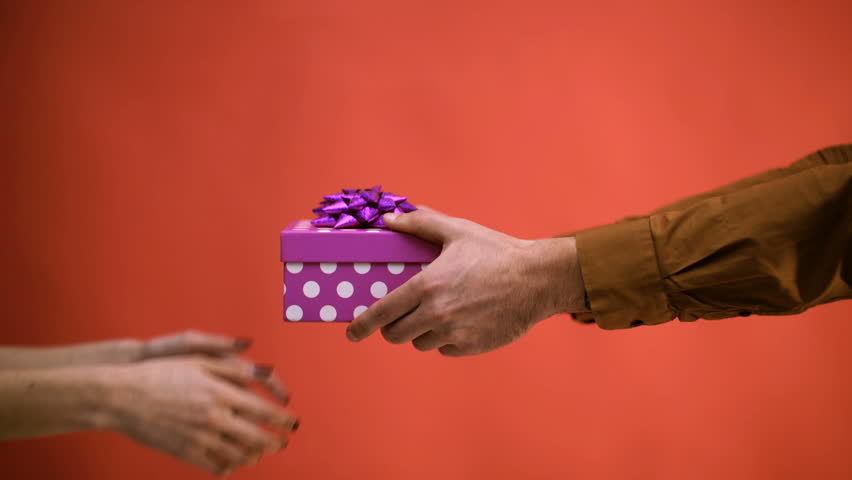 Close up of male hands giving a Christmas gift to girlfriend. Closeup picture of man's and woman's hands with gift box. Marry Christmass and Happy New Year. Seasonal greetings for winter | Shutterstock HD Video #1029185387