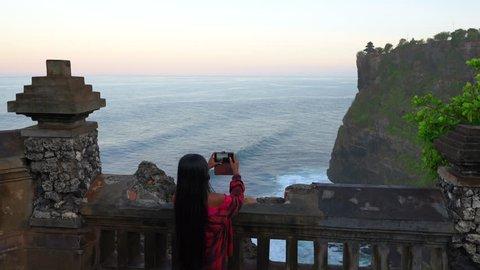 Active lifestyle woman make photo popular tourist attractions island Bali balinese hindu Uluwatu Temple Indonesia