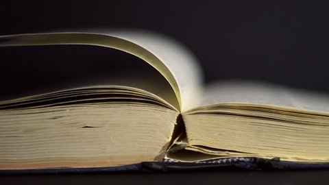 Slow motion, close up of an old, vintage, open book with pages turning on the wind, on a dark room with few light, with black surroundings