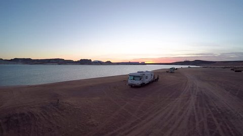 Aerial shot rising over the stunning Lake Powell at sunset, with RV's and motorhomes camping along the shoreline