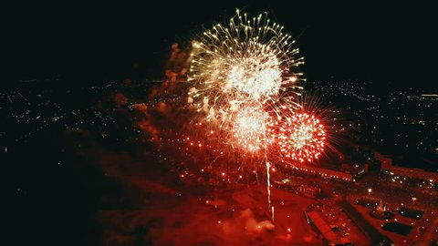 Fireworks in the City Sky. Aerial Drone Scene. City Night Lights. The Camera Rotates in a Semicircle and it is seen how the fireworks explode. 4K footage.