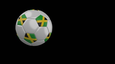 Soccer ball with the flag of Jamaica flies past the camera, slow motion, 4k footage with alpha channel