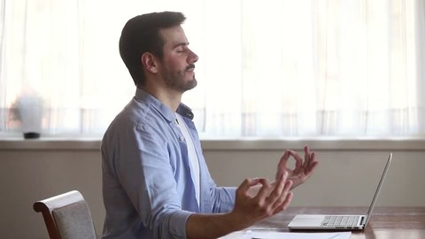 Calm mindful young man taking break sit at home office desk meditating doing exercise feel no stress free relief relaxing, healthy serene guy practicing yoga breathing for peaceful mind and zen