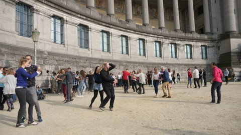 Brussels, Belgium - April 1, 2019:Cheerful view of energetic adult people dancing outdoors at a high historic building with columns on a sunny day in spring in slow motion