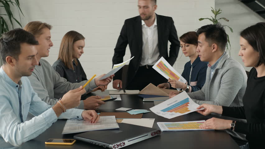 Hot discussion in the meeting. Serious business partners are using brainstorm method to achieve success in their start up boss coming and start meeting boss coming | Shutterstock HD Video #1029346547