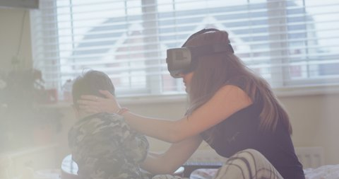 Teenager girl while using a VR playing on the bed with her small brother , happy they spend a funny time together