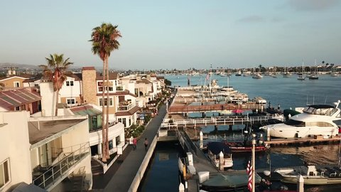 Drone View of Newport Beach, Balboa Peninsula, and Newport Coast in Orange County, California. Ships, boats, sail boats, and beach homes are revealed from the clouds from this Aerial Approach.